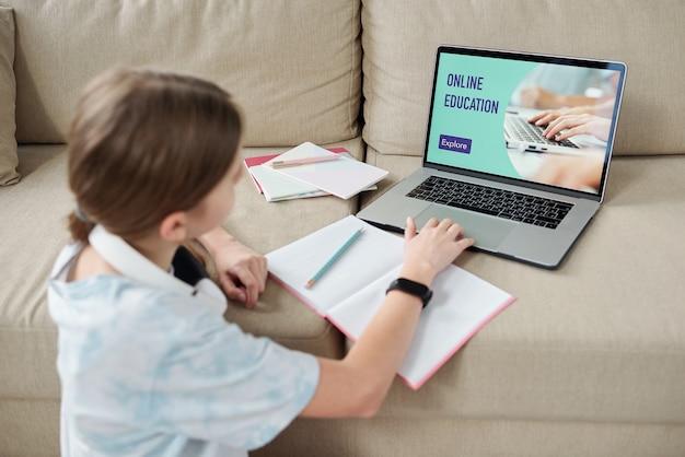 現代のティーンエイジャーは、前にラップトップを持ってソファに座って、自宅の検疫中にリモートコンピューターを介してオンラインで勉強しています