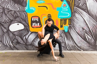 Contemporary urban street dancer dancing in front of graffiti