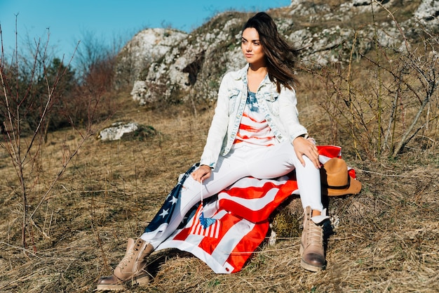 Contemporary woman with usa flag sitting in nature
