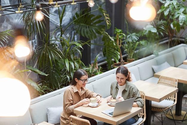 Contemporary women enjoying coffee in outdoor cafe