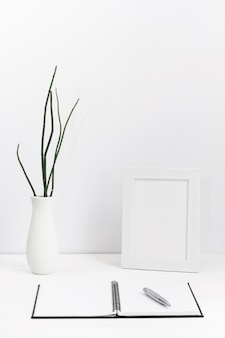 Contemporary work space with blank agenda and vase with frame