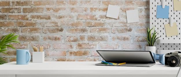 Современное рабочее пространство с канцелярскими принадлежностями для камеры ноутбука и расходными материалами на столе и кирпичной стене 3d-рендеринга