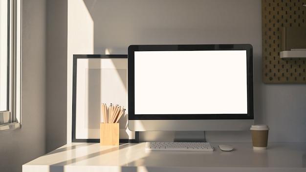 コンピューター、コーヒーカップ、鉛筆ホルダー、白いテーブルの上の空のフォトフレームを備えた現代的なワークスペース。