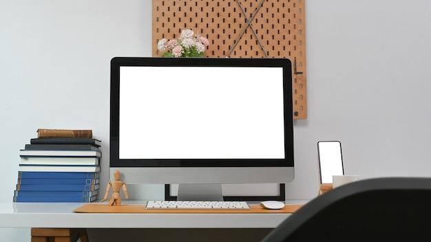 Современное рабочее место с компьютером, смартфоном и канцелярскими принадлежностями на белом столе.