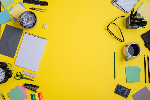 Contemporary workspace with supplies on yellow background