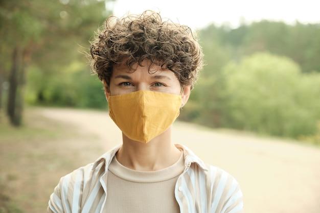보호용 수제 마스크를 쓴 현대의 젊은 브루네트 여성이 자연 환경에 서 있는 동안 당신을 바라보고 있습니다