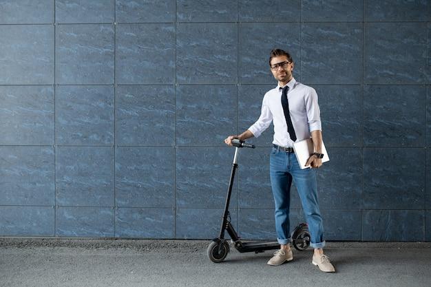 ブルージーンズ、白いシャツ、スクーターと都市の建物の壁のそばに立っているラップトップと黒のネクタイの現代的な青年実業家