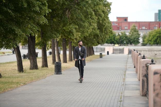 도시 환경에서 강변과 공원을 따라 전기 스쿠터를 타는 스마트 캐주얼웨어의 현대 젊은 사업가