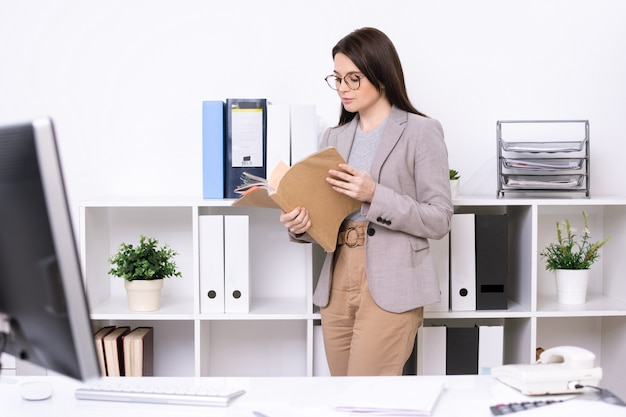 Contemporary young businesswoman or accountant looking through financial papers while standing by shelves in office