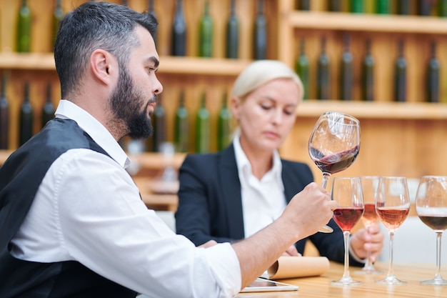 Contemporary young cavist checking quality and characteristics of new sorts of wine while working