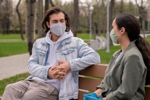 캐주얼웨어와 나무 벤치에 앉아 보호 마스크에 현대 젊은 부부