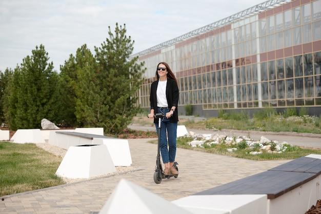Современная молодая элегантная деловая женщина, стоящая на электросамокате во время движения в городской среде на фоне современной архитектуры