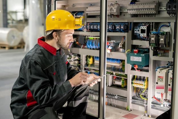 Современный молодой инженер в спецодежде и каске просматривает данные на планшете, сидя на корточках у одной из промышленных машин