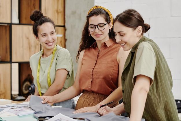 현대 젊은 여성 패션 디자이너들이 시즌 컬렉션 아이템 중 하나에 텍스타일을 선택하고 적합한 지 논의