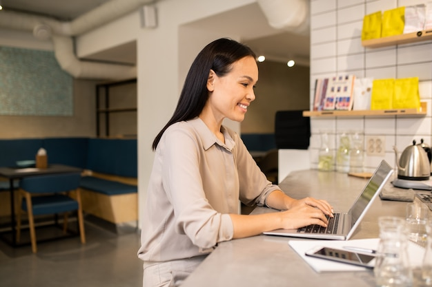 Современная молодая владелица кафе или ресторана сидит за ноутбуком в конце рабочего дня и составляет план на следующий день