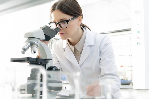 Современная молодая женщина-исследователь в очках и белом халате смотрит в микроскоп во время изучения covid19 в научной лаборатории
