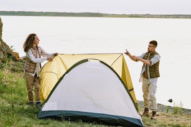 Современные молодые туристы ставят палатку на землю у воды и натягивают текстильную крышу поверх нее, готовясь к ночи