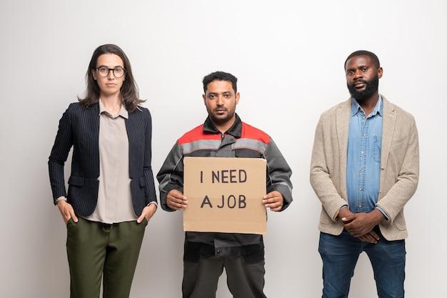 직업이 필요한 것에 대해 제복을 입은 노동자가 메모를 들고있는 동안 카메라 앞에서 벽에 서있는 현대 젊은 이문화 실업자