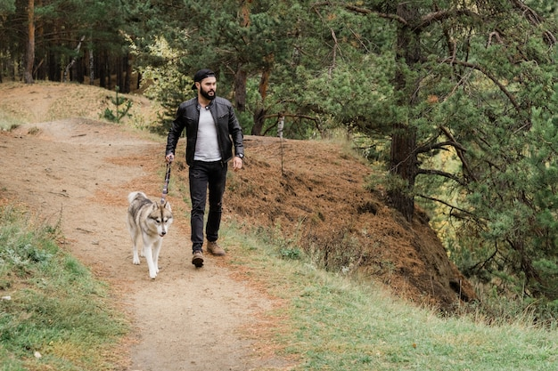 Contemporary young man in casualwear walking down footpath while holding leash of his purebred dog