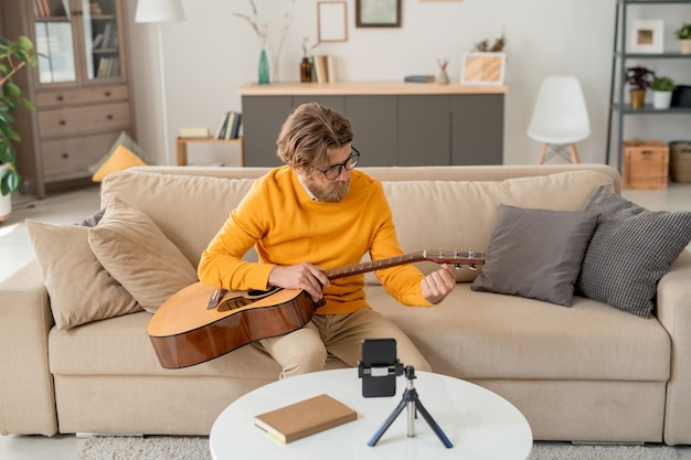 Современный молодой человек в джинсах и желтом джемпере сидит на диване и дергает за струны гитары перед камерой смартфона дома