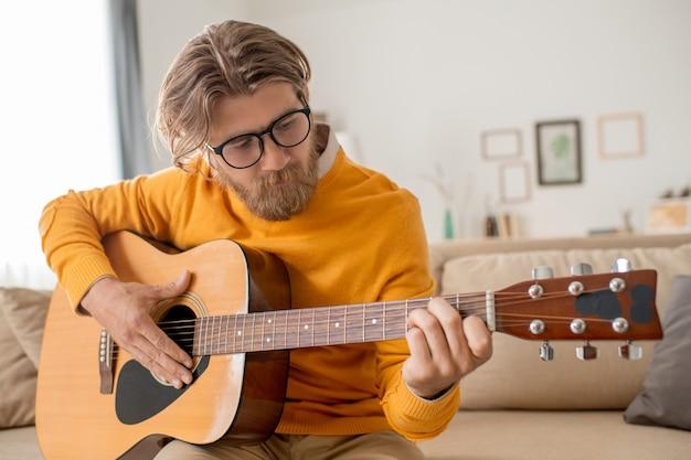 청바지와 노란색 점퍼가 소파에 앉아 집에서 스마트 폰 카메라 앞에서 기타 문자열을 당기는 현대 젊은 남자