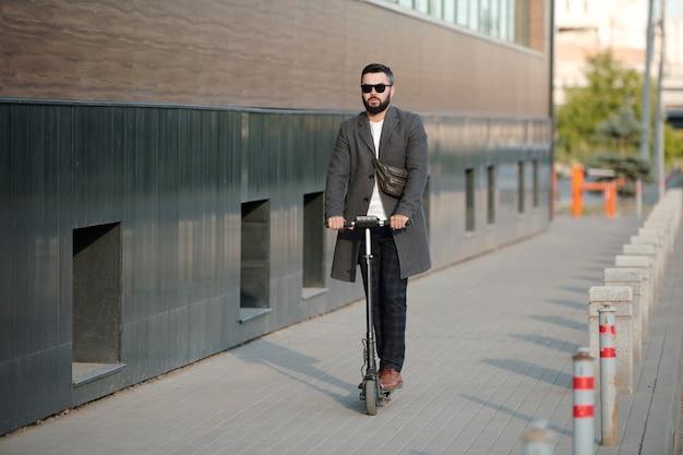 현대 건축의 벽을 따라 이동하면서 전기 스쿠터에 서있는 바지, 코트 및 선글라스의 현대 젊은이