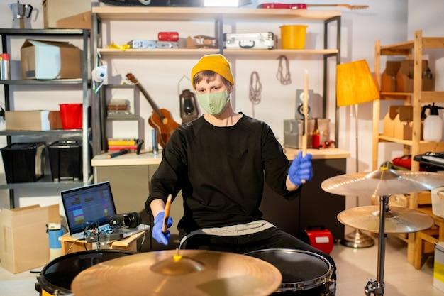 드럼 세트 앞에 앉아 새로운 음악을 만드는 동안 보호 장갑과 마스크를 들고 나지만 현대 젊은 남자