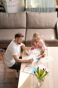 Современный молодой человек учит свою маленькую дочь рисовать цветными карандашами, сидя за деревянным столом в гостиной