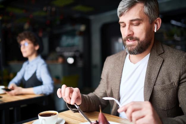 Airpodとスマートカジュアルなカフェに座っているとランチのデザートを食べる現代の若い男 Premium写真