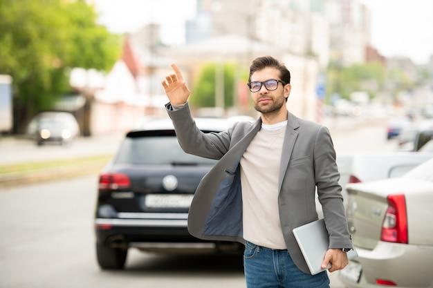 Современный молодой человек с ноутбуком стоит у дороги с поднятой рукой, ловя такси утром