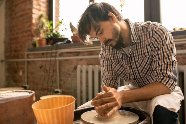 職場のそばに座って陶器のホイールで液体粘土の新しいアイテムを作る陶芸の現代的な若いマスター