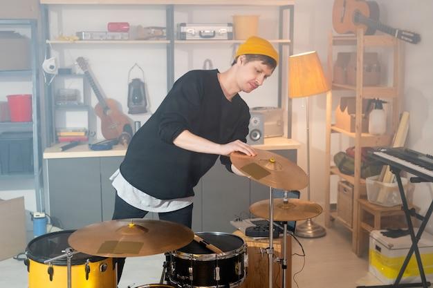 차고에서 개별 리허설하기 전에 심벌즈 중 하나를 확인하면서 드럼 키트를 구부리는 캐주얼웨어의 현대 젊은 음악가
