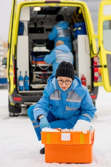屋外の応急処置キットで薬を探している青い作業服と手袋の現代の若い救急救命士