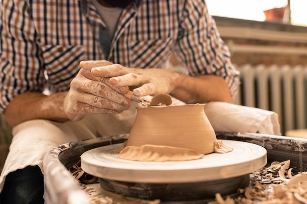 Современный молодой гончар выравнивает дно новой глиняной чаши специальным ручным инструментом, наклоняясь над кругом