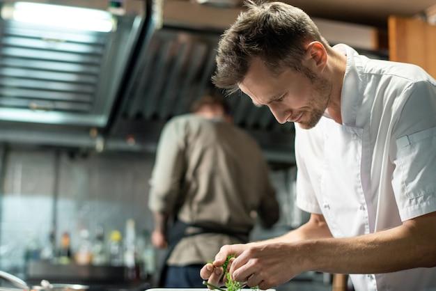 野菜や肉を飾るために緑のディルやパセリを選んでいる間、台所のテーブルの上に曲がっている現代の若いプロの男性シェフ