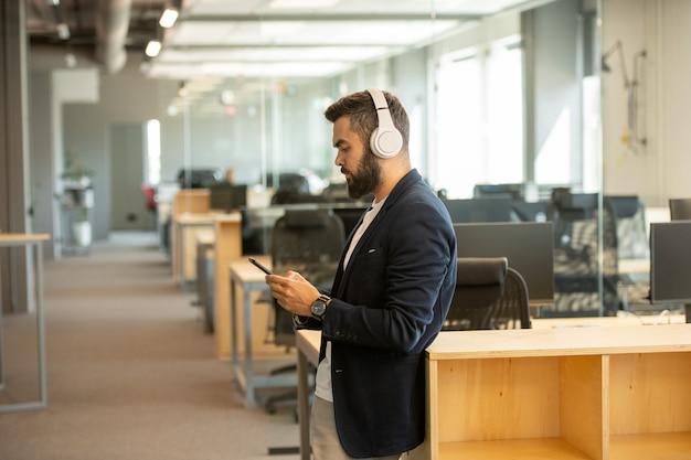 Openspace에서 책상의 행에 서있는 동안 스마트 폰에서 스크롤하는 헤드폰을 가진 현대 젊은 심각한 회사원