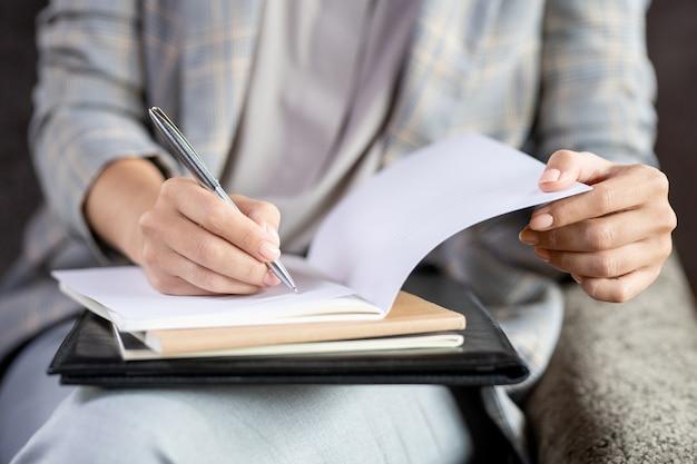 学生の一人の紙をチェックしながら開いているコピーブックのページの上にペンを置く現代の若い先生