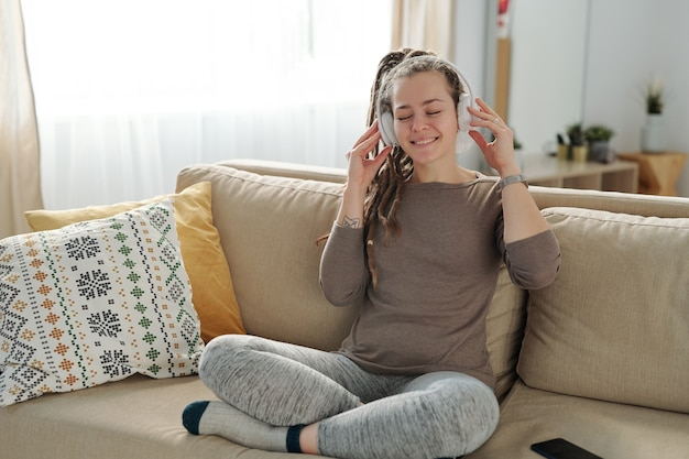 Contemporary young woman with dreadlocks enjoying music in headphones while sitting on couch at home