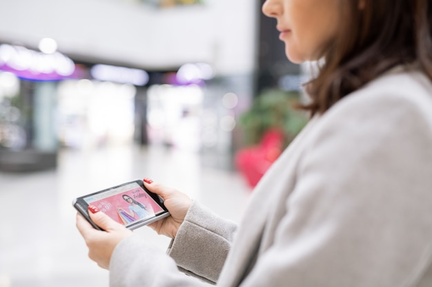 Contemporary young woman with smartphone surfing in online shop during seasonal sale while standing in the mall