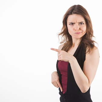 Contempt young woman pointing at something against white background