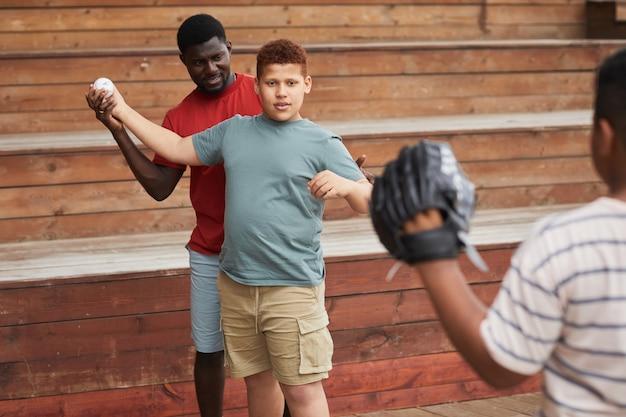 내용 아프리카계 미국인 아버지가 아들에게 투구를 가르치는 동안 팔을 조정하고 있습니다.