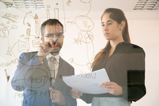 コンテンツアフリカ系アメリカ人マネージャーがガラス板にグラフを書きます。ドキュメントを保持し、会議室でグラフを見てプロの若いかなり女性の同僚。チームワークとマーケティングの概念