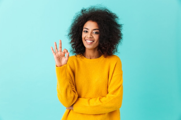 Content american woman in colorful shirt smiling  and gesturing ok sign, isolated over blue wall