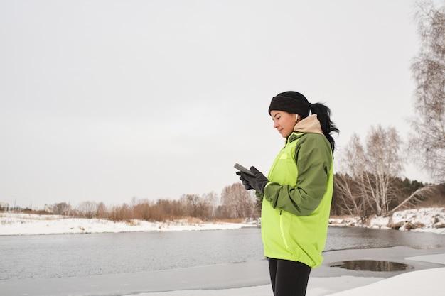 Довольная привлекательная бегунья в наушниках, стоящая на берегу реки и проверяющая фитнес-приложение на телефоне