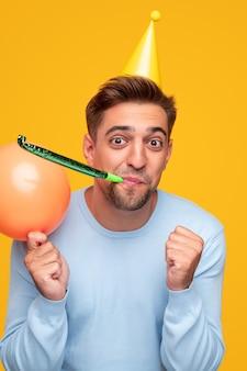 バルーンを保持し、黄色の背景にパーティーホーンを吹く誕生日を祝うパーティーハットのコンテンツひげを生やした男性