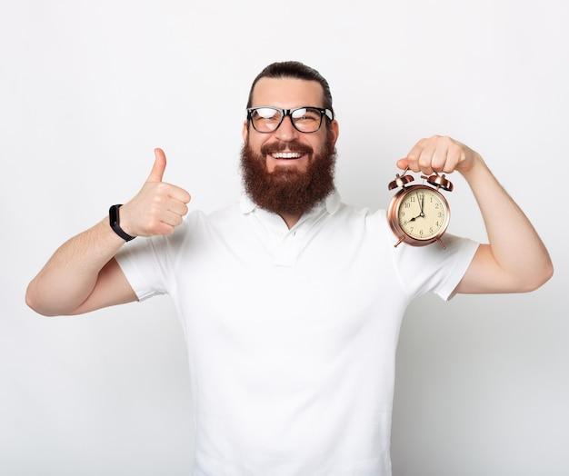 ひげを生やしたコンテンツの男は、ジェスチャーや目覚まし時計のように表示されています。