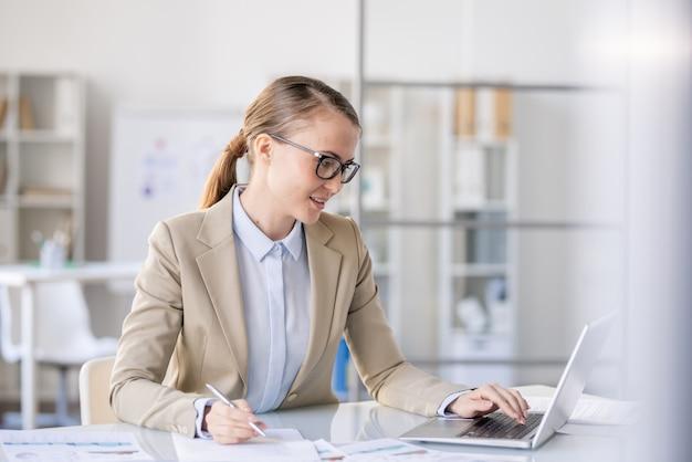 Довольная красивая бизнес-леди с хвостиком сидит за столом и анализирует продажи при подготовке отчета и использовании ноутбука в офисе