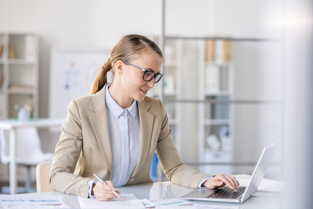 Content beautiful business lady with ponytail sitting at table and analyzing sales while preparing report and using laptop in office