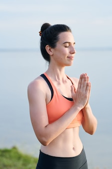 Content beautiful girl in sports bra keeping hands in namaste while thanking body and soul after yoga practice