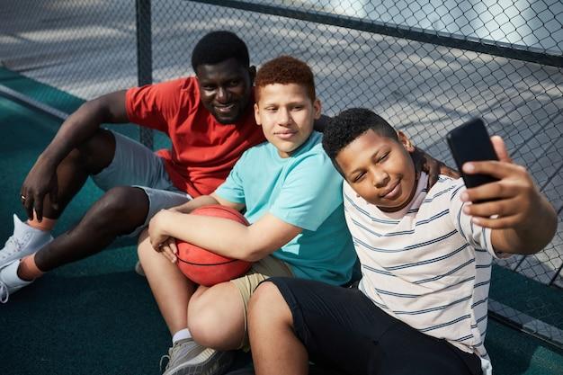 バスケットボールの後に父と弟と一緒に自分撮りをしながら地面に座ってスマートフォンを使用してコンテンツ黒人の少年